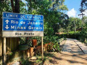 Placa sinalizando a divisa de estadp de Minas gerais com Rio de Janeiro na estarda para Visconde de Maua