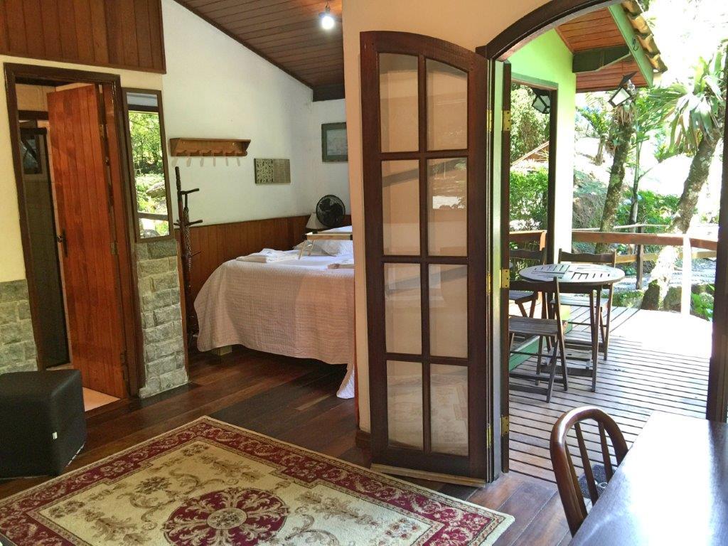 Interior de um chalé com varanda e cama de casal em Maromba