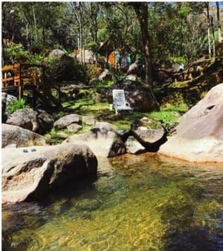 Pousada com ccachoeira passando no jardim na vila da Maromba