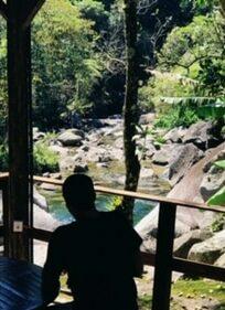 Homem de costas olhando o rio em Visconde de Maua