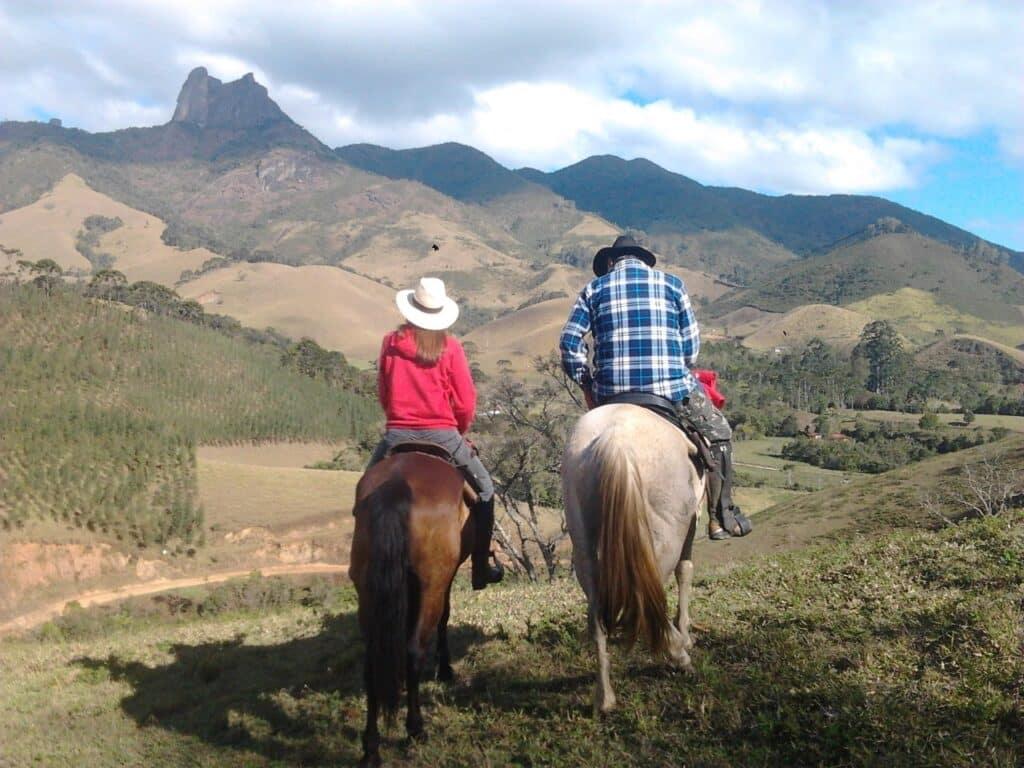 Casal em em cima de cavalos e montanhas ao fundo em Visconde de Mauá