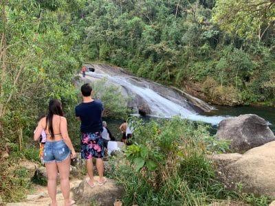 Casal na trilha para a cachoeira ao fundo em Visconde de Mauá